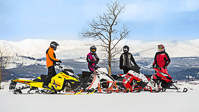 Group of four snowmobilers standing by snowmobiles in winter.