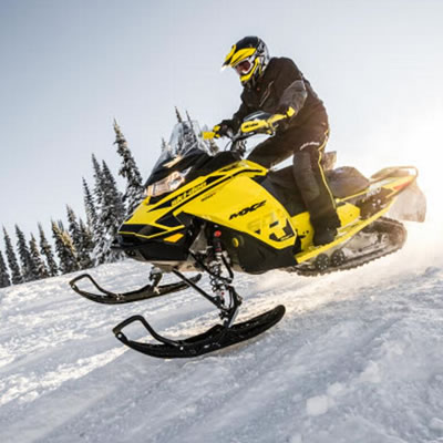 Person riding a yellow snowmobile.