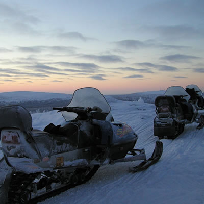 Snowmobiles with sunset in background.