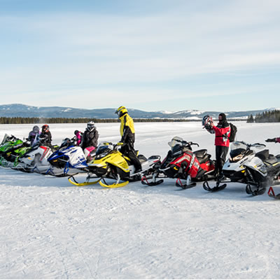 Group of snowmobilers lined up in a row.