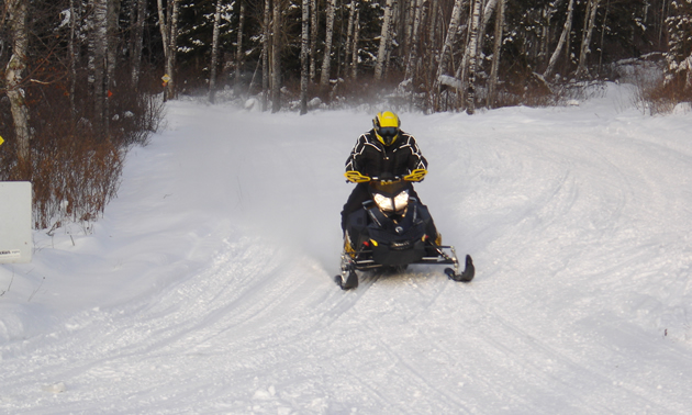 A snowmobiler coming down a snowmobile trail.