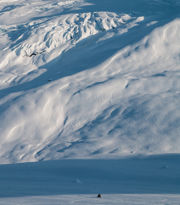 Ben Fagen on his snowmobiling looking up at a massive wall of snow near Valdez, Alaska.