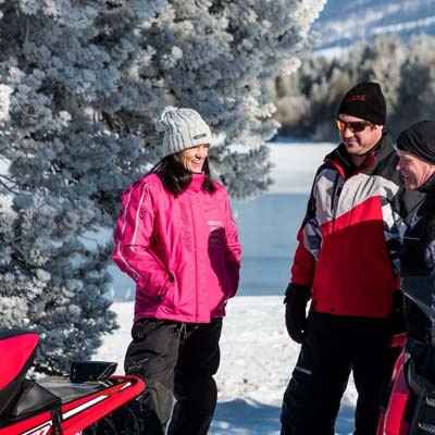 Group of snowmobilers talking to each other.