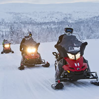 Three people on snowmobiles in Northern Sweden.