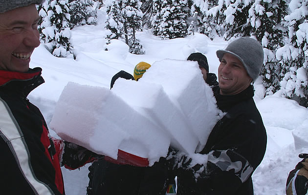 A man in a grey toque carrying some slabs of snow.