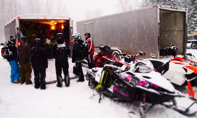 A group of snowmobilers discussing things at the trailer before they ride.