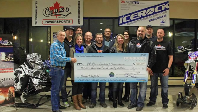 Organizers from the Vernon Snow Show hold up a large cheque for the Easter Seals Snowarama Kids campaign.