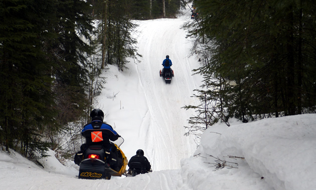Snowmobilers going through some twisties on the trails in Whitecourt.