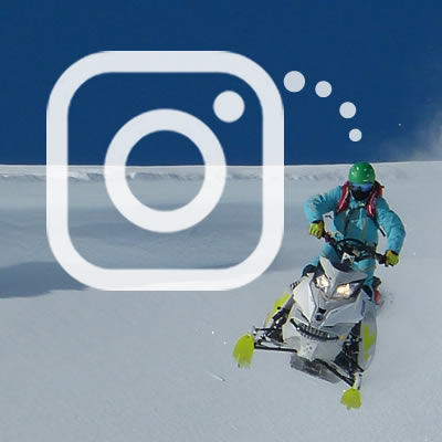 A snowmobiler dropping a cornice with the SnoRiders instagram logo on the photo.