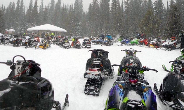 A large group of snowmobilers parked around the cabin.