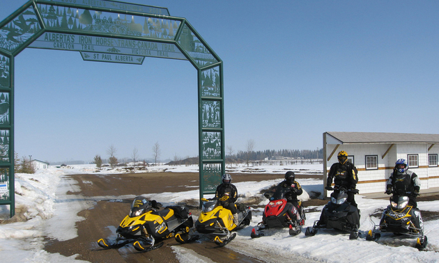 sledders in front of a trail sign ready to ride