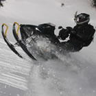 A man in black on a black snowmobile.