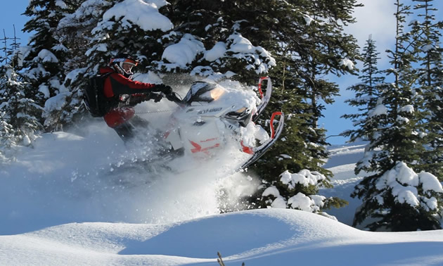 A snowmobiler on a white Ski-Doo busting through the pow.