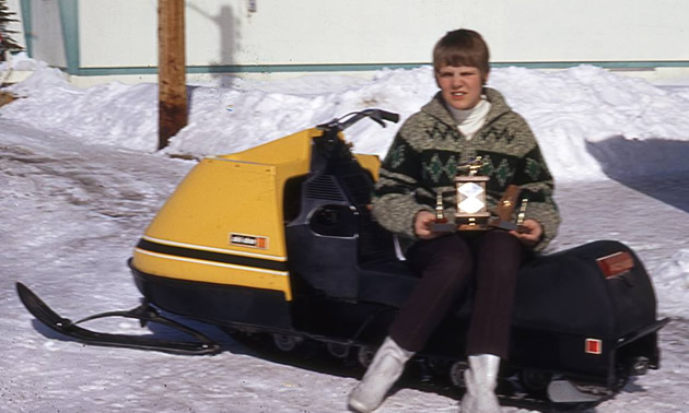 Picture of 13-year old Sue Thomas, sitting on snowmobile and holding trophy.