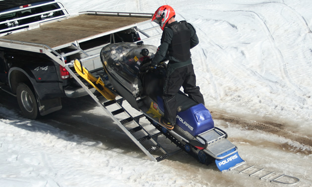Photo of a man loading a snowmobile onto a trailer.