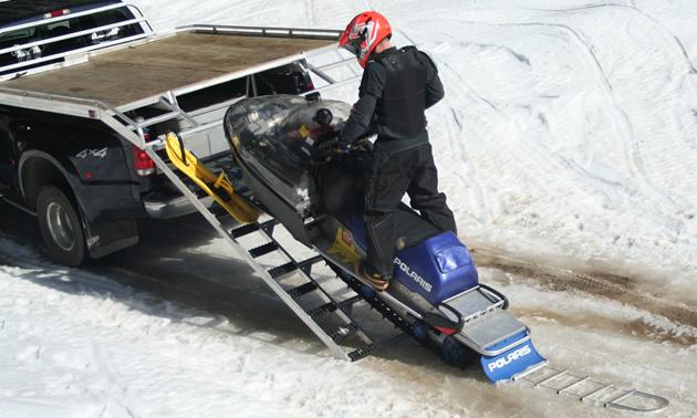 Photo of a man loading a snowmobile onto a trailer.