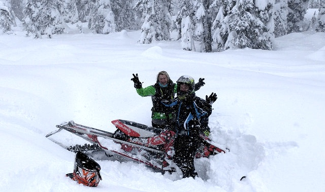 Susan Lohrer experiencing her first creek drainage stuck with a helping hand from her sled sister Trish Drinkle.