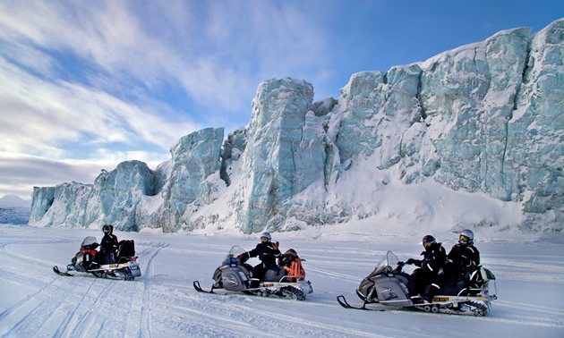 snowmobiles by a large mountains of ice in Norway.