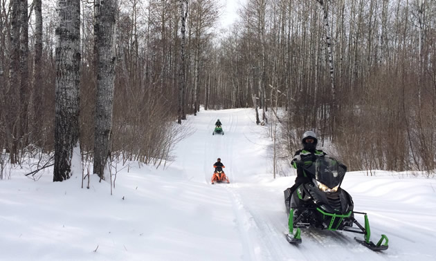 Three snowmobilers heading up the trail.