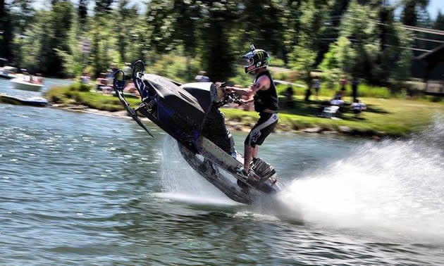 Taylor Fisk wheelies his sled across the water.
