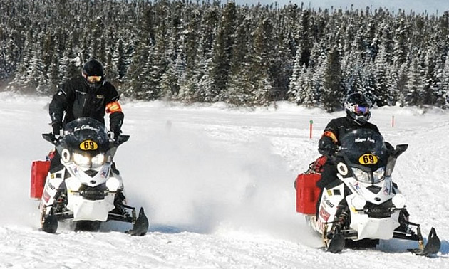 Two snowmobile racers neck and neck.