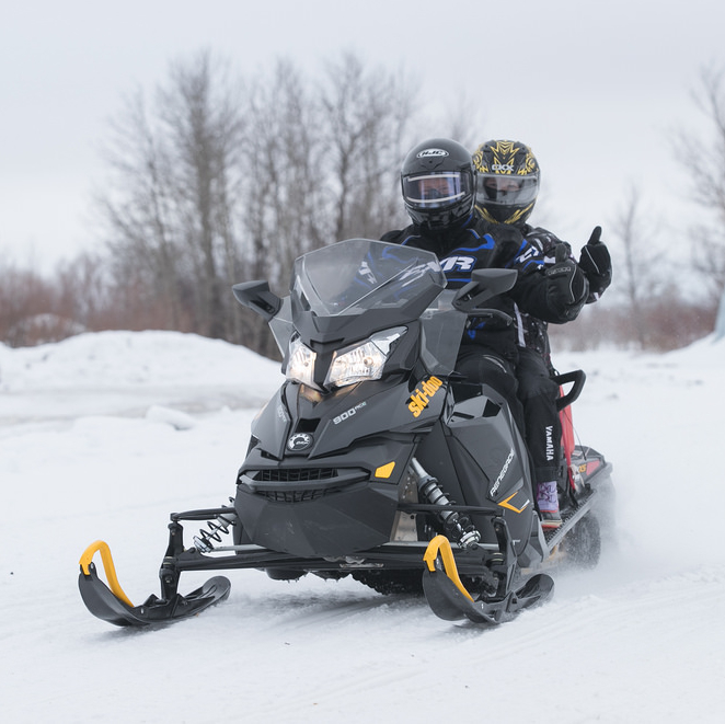 two snowmobilers riding on a plain with trees in the background...one sledder is giving a thumbs up sign