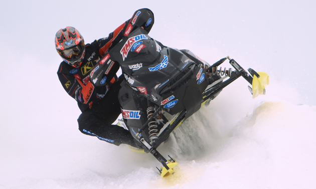 Tim Tremblay snocross racer leans to the inside of his black sled in a snocross race.