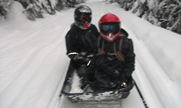 Two kids sitting in a toboggan behind a snowmobile.