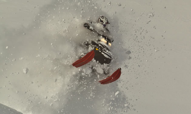 A guy on a black sled busting through the pow.