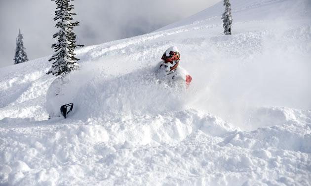 A snowmobiler slashes into the deep snow around Revelstoke.