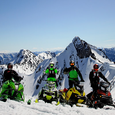 A group of snowmobilers on bc mountains.