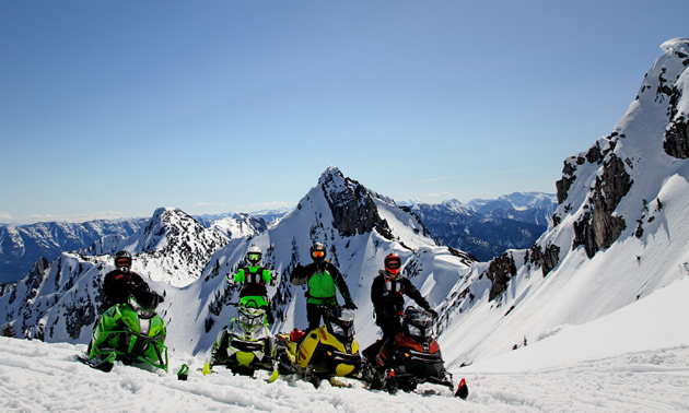 Four snowmobilers wave on a clear day in the mountains.