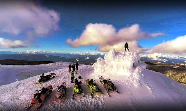 A group of snowmobilers on top of a lookout.