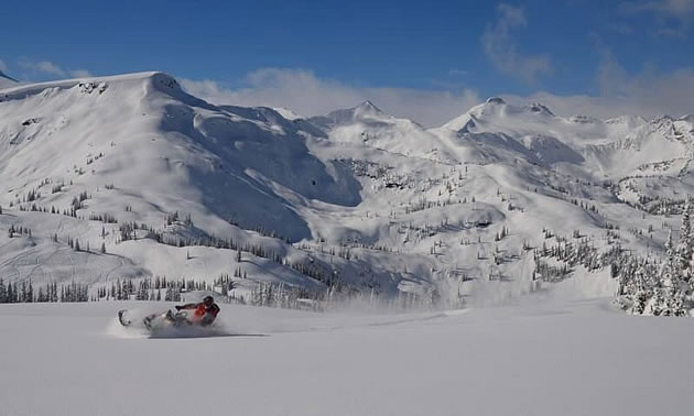 A snowmobiler in a mountain bowl.