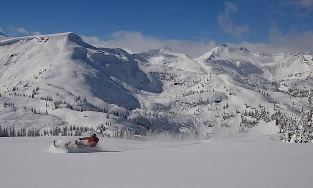 A snowmobiler in a mountain bowl.