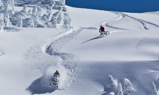 Two snowmobilers carving a line downhill in Whistler.