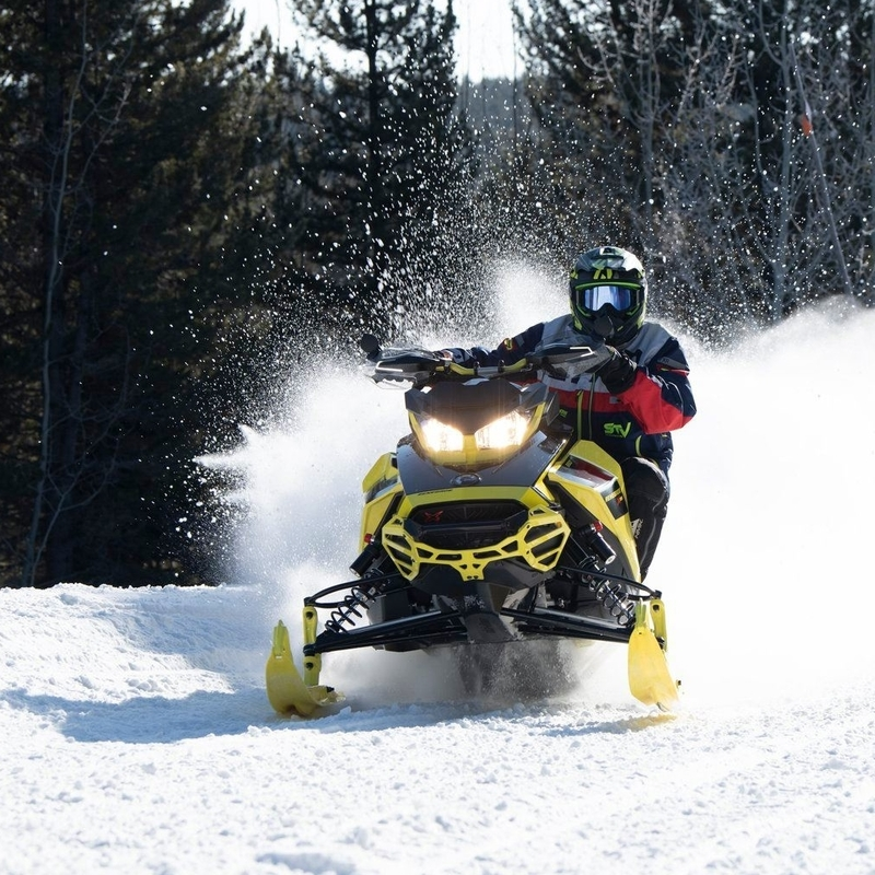 person riding a snowmobile on the trail