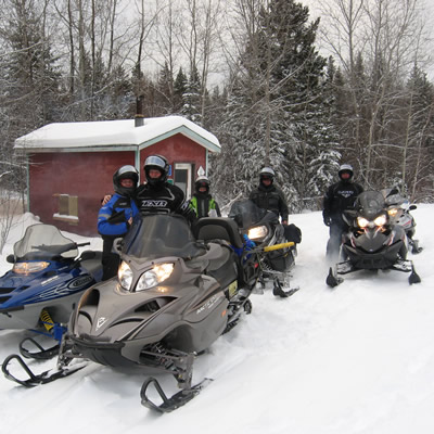 A group of sledders stopped by a red cabin on the trails in The Pas.