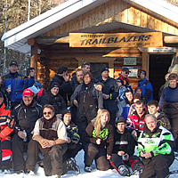 A group of snowmobilers standing in front of a cabin in Whitecourt.