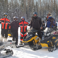 A group of people in snowmobile suits standing together.