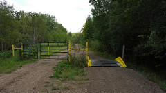 Part of the trail with a gate on the left and a ramp on the right for ATVs to cross.