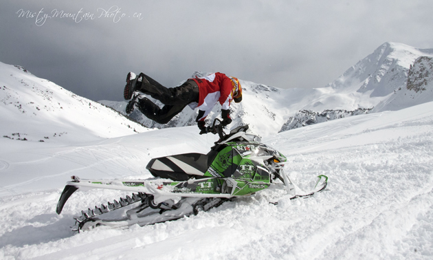 A woman doing a superman move on a parked snowmobile.