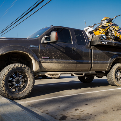 A truck with a deck and two sleds.