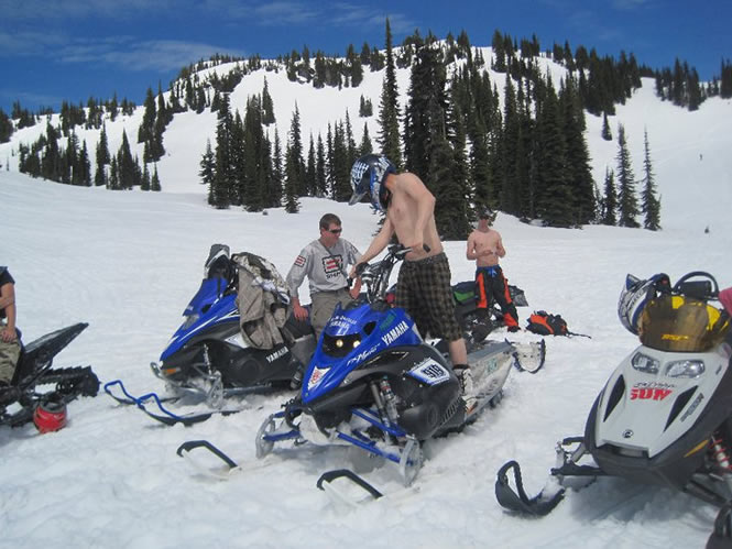 men with no shirts on riding sleds