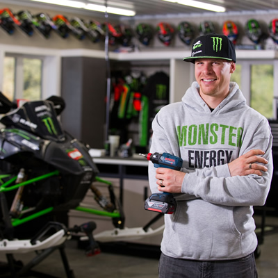 Picture of Tucker Hibbert standing with Bosch drill in his hand, with snowmobile in background.