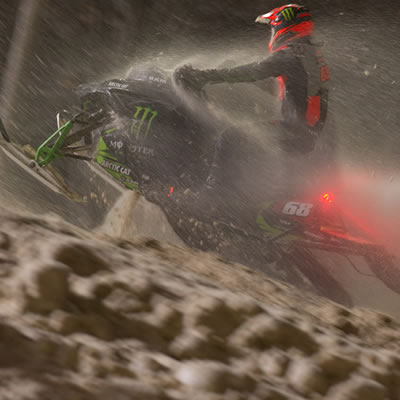 Tucker Hibbert on his snowmobile, night scene.