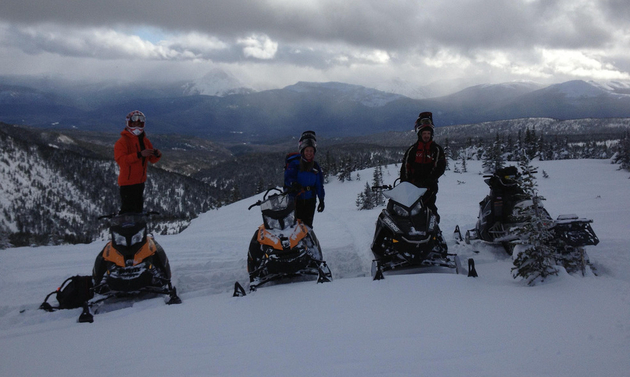 Four sledders are in front of a spansive mountain view in the Babcock riding area.