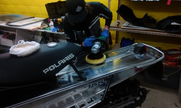 Trish Drinkle polishing the aluminum tunnel on a sled.