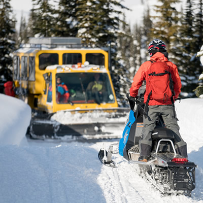 A snowmobiler is on a trail, facing a snowcat, and has no room to pass by.