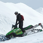 A guy on a green snowmobile riding down a ridge with a snow-covered mountain in the background.